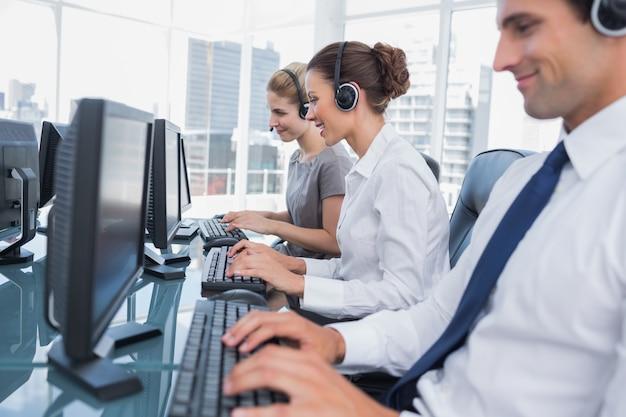 Groep callcentermedewerkers die in lijn werken