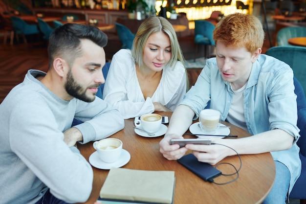 Groep casual college vrienden zitten aan tafel in café na de lessen, koffie hebben en nieuwsgierige dingen in smartphone kijken