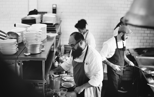 Groep chef-koks die in de keuken werken