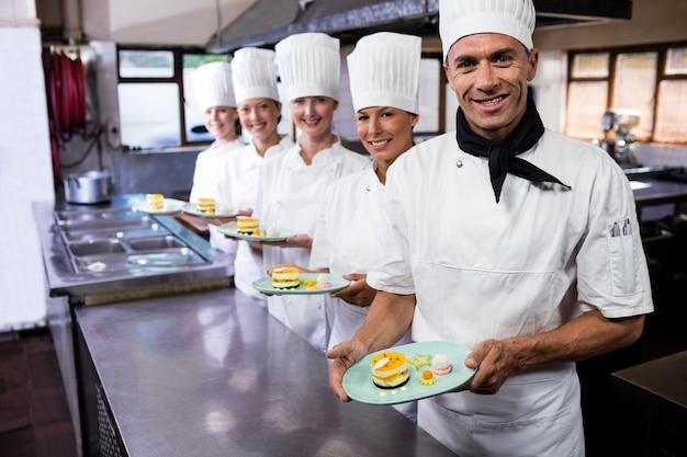 Groep chef-koks die plaat van heerlijke desserts in keuken houden