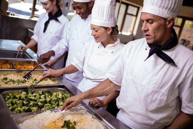 Groep chef-koks die prepard voedsel in keuken bewegen