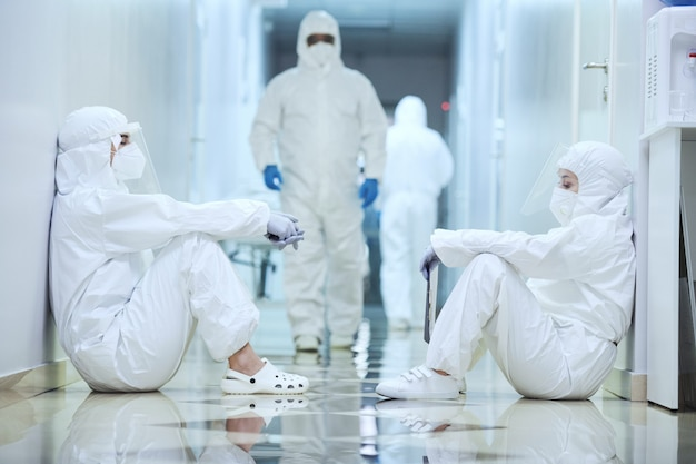Groep chirurgen in beschermende uniformen die in de gang in het ziekenhuis zitten en werken tijdens de pandemie