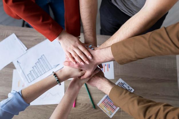 Groep collega's die hun handen in elkaar zetten