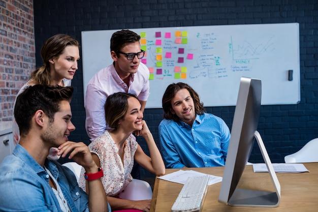 Groep collega's die op een computer letten