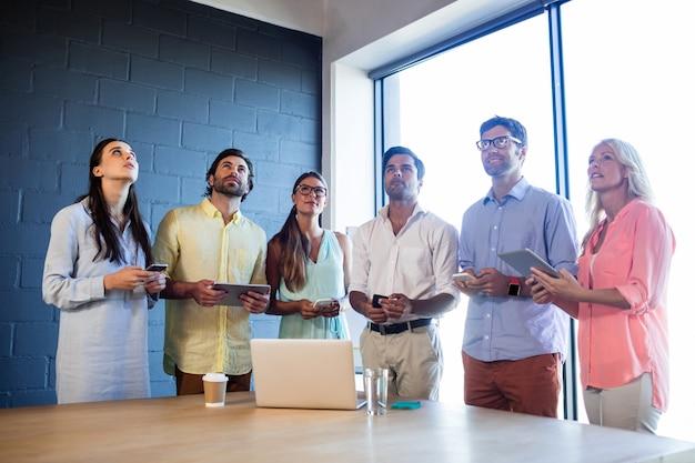 Groep collega's gebruikend laptops en smartphones en omhoog kijkend