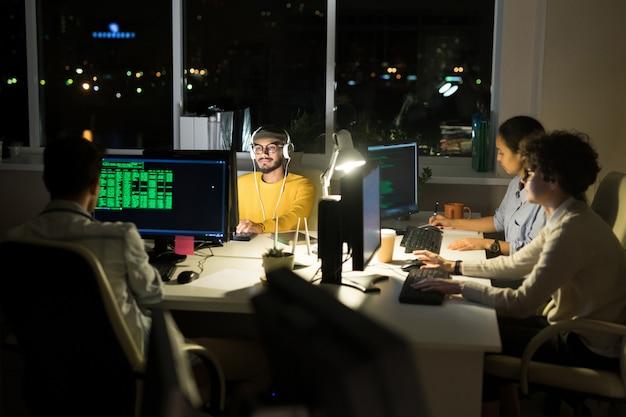 Groep computerprogrammeurs die bij nacht coderen