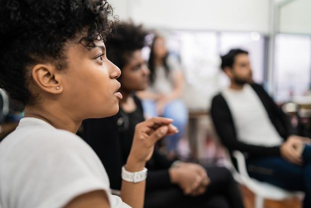 Groep creatieve bedrijfsmensen die aan collega luisteren die bureauvergadering aanpakken. bedrijfs- en brainstormconcept.