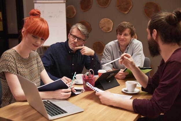 Groep creatieve mensen die het resultaat van werk analyseren