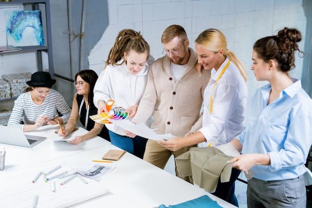 Groep creatieve modeontwerpers bespreken kleuren, textiel en schetsen tijdens het werken door bureau in de studio