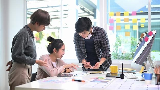 Groep creatieve ontwerpers die brainstormen en een nieuw projectplan bespreken in een modern kantoor.