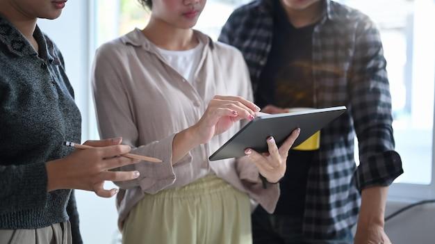 Groep creatieve ontwerpers die digitale tablet gebruiken en een nieuw projectplan bespreken op een modern kantoor.
