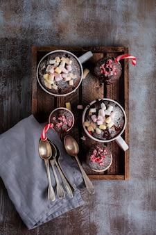 Groep de chocoladetaart van het nieuwjaar die in microgolfoven in mok op uitstekende grijze oppervlaktetextuur wordt gekookt