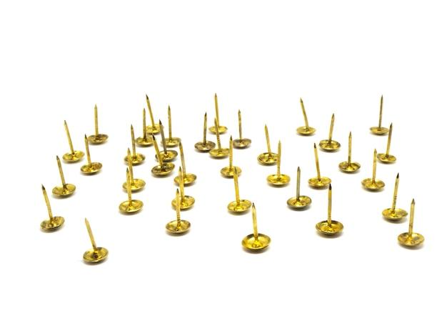 Groep de gouden kopspijker van de metaalduim op geïsoleerde witte achtergrond