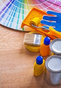 Groep de hulpmiddelen van het verfhuishouden en de gids van het kleurenpalet op het houten concept van de raadsbouw