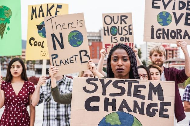 Groep demonstranten op weg uit verschillende culturen en rassen vechten voor klimaatverandering - focus op afrikaanse vrouw