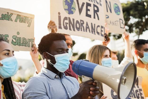 Groep demonstranten op weg uit verschillende culturen en rassenprotesten voor klimaatverandering tijdens de uitbraak van het coronavirus - focus op het gezicht van de afro-amerikaanse man