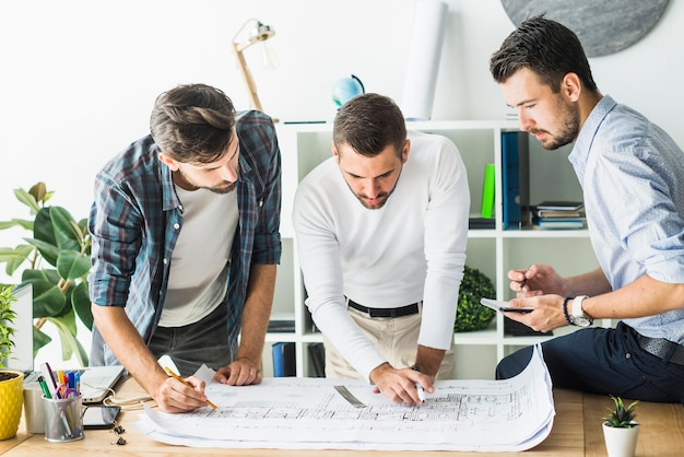 Groep die mannelijke architect blauwdruk analyseren