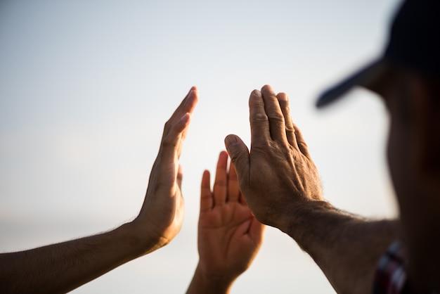 Groep die mensen hand geven die eenheid en groepswerk tonen.