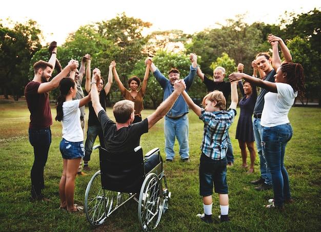 Groep die mensen hand in het park samenhoudt