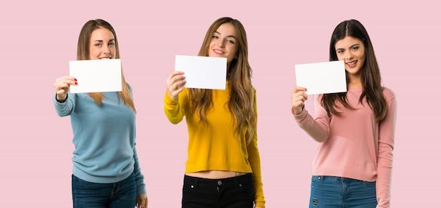 Groep die mensen met kleurrijke kleren een leeg wit aanplakbiljet op kleurrijke achtergrond houden