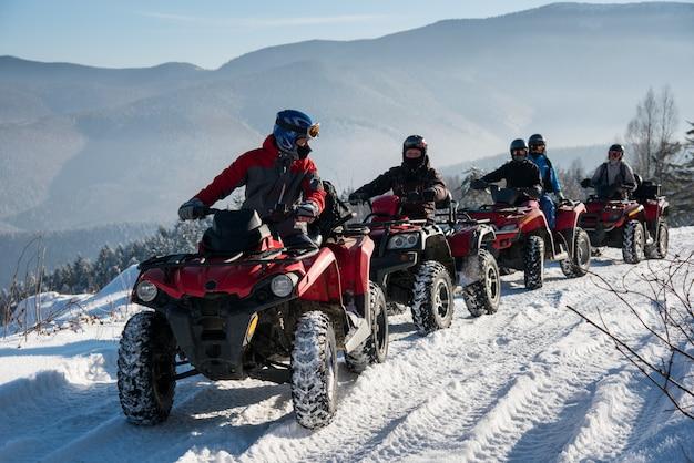 Groep die mensen off-road vierlingfietsen drijven op sneeuw boven de berg in de winter