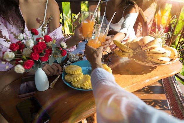 Groep die mensen ontbijt samen het toejuichen van glazen eten