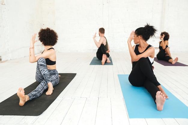 Groep die mensen yoga in gymnastiekzitting doen op opleidingsmatten
