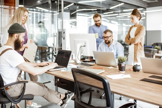 Groep diverse collega's die op de computers werken in de moderne kantoor- of coworking-ruimte, bebaarde hipster als programmeur die code schrijft