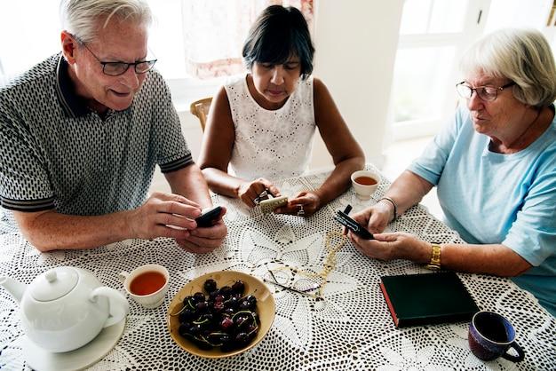 Groep diverse hogere mensen die mobiele telefoon met behulp van