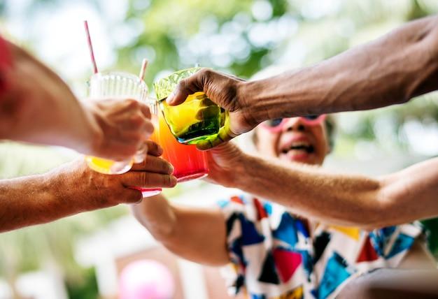Groep diverse hogere volwassene die van drank genieten door de pool samen