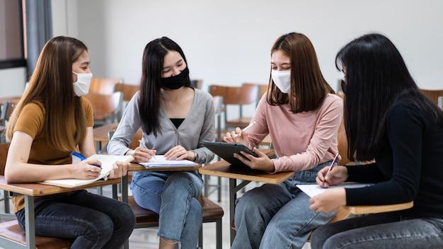 Groep diverse internationale studenten die beschermende maskers dragen en praten, een project bespreken, aan een bureau zitten in de klas op de universiteit