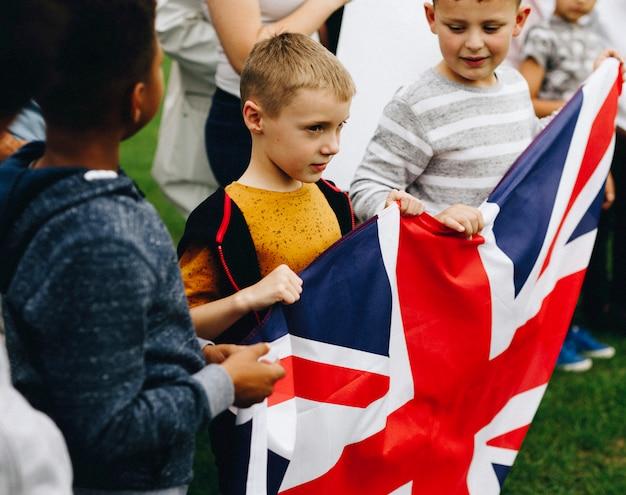 Groep diverse kinderen die een britse vlag in een protest tonen