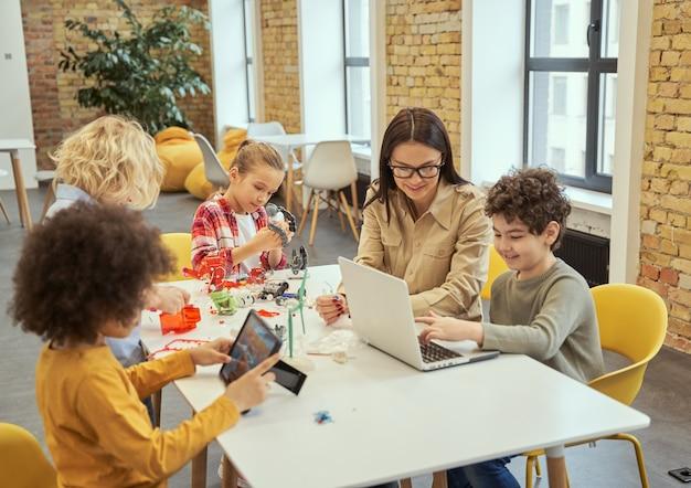 Groep diverse kinderen die samenwerken met een jonge vrouwelijke leraar die tijdens de stam aan de tafel zit