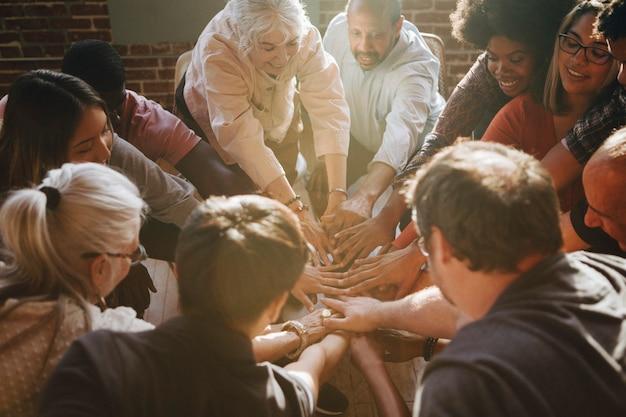 Groep diverse mensen die handen in het midden stapelen