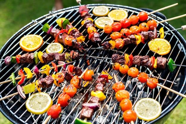 Groep diverse vrienden die barbecue in openlucht roosteren