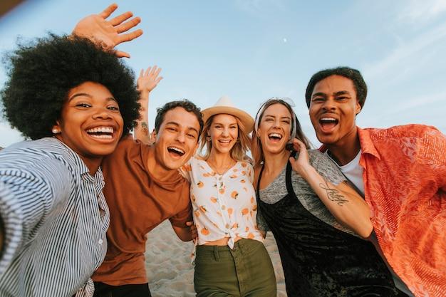 Groep diverse vrienden die een selfie nemen bij het strand