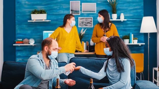 Groep diverse vrienden die handdesinfecterende gel en beschermende maskers gebruiken die vieren op een nieuw normaal feest