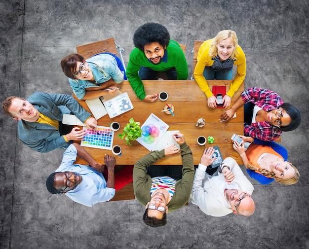 Groep diverse vrolijke ontwerpers die omhoog eruit zien