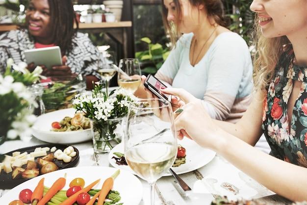 Groep diverse vrouwen die maaltijd hebben die samen digitale apparaten met behulp van