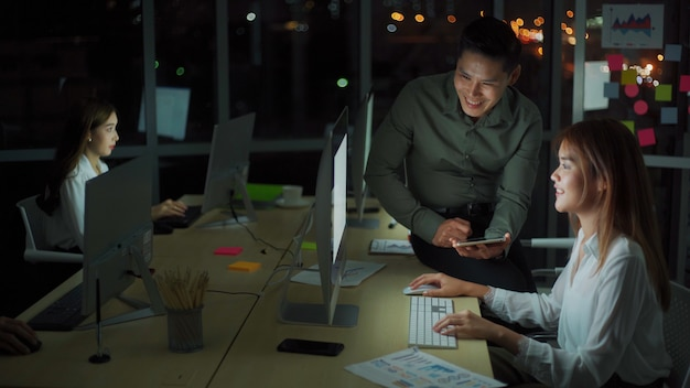 Groep diversiteit mensen team werken laat in kantoor 's nachts. twee blanke mannen en een aziatisch meisje voelen zich gelukkig en succesvol voor nieuwe zaken. werken 's avonds laat en overuren concept