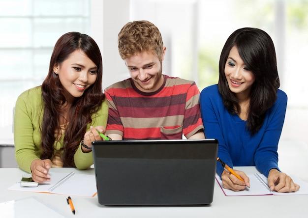 Groep diversiteits gelukkige studenten die samen gebruikend laptop bestuderen