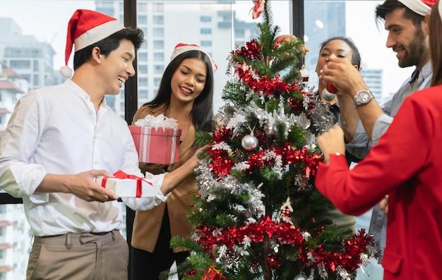 Groep diversiteits jonge creatieve gelukkige vierende vrolijke kerstmis en gelukkig nieuwjaar die kerstboom in bureau in modern bureau verfraaien