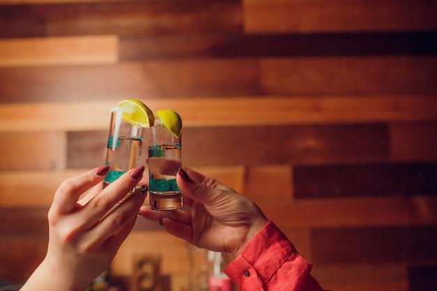Groep dronken vrienden die cocktails roosteren bij barrestaurant