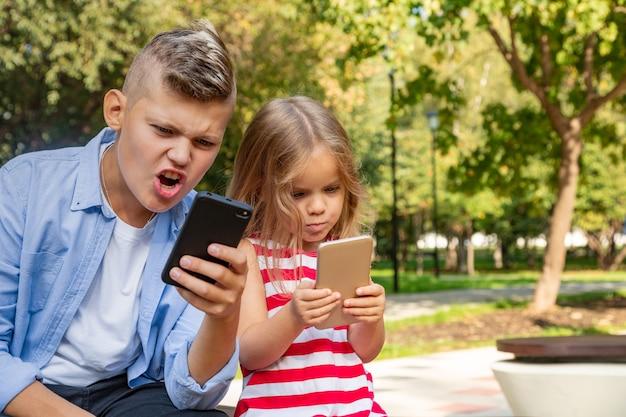 Groep drukke kinderen kijken naar hun telefoons sms'en sms en spelen buiten zitten