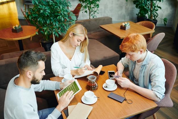 Groep drukke studenten zitten aan tafel in café na de lessen, jongens met behulp van gadgets terwijl blond meisje aantekeningen maken in kladblok