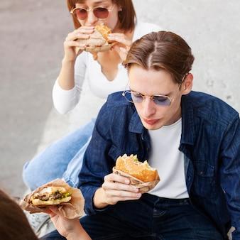 Groep duivels die hamburgers buitenshuis eten