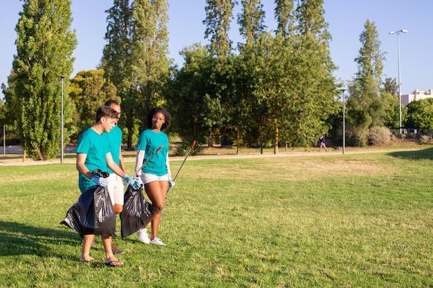 Groep ecovrijwilligers die park verlaten na het schoonmaken van gazons