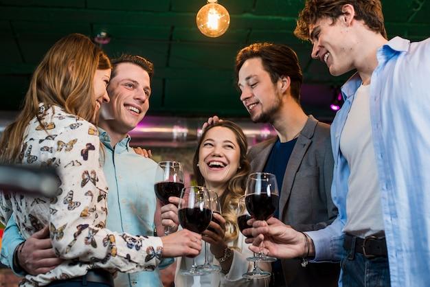 Groep een gelukkige vrienden die avond van dranken in bar genieten