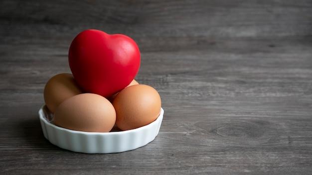 Groep eieren met rood ballenschuim in vormhart in schotel op houten vloer.