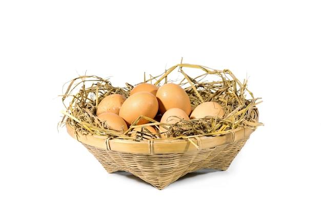 Groep eieren met stro in een bamboemand die op wit wordt geïsoleerd